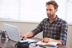 Writer busy digitalising his work from handwritten notebook to laptop. Young caucasian male writer busy digitalising his latest novel from handwritten notebook royalty free stock image