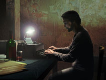 Writer in the dark. Innside a dark and dirty room, under the light of a little lamp, a seated man is typing at his typewriter Royalty Free Stock Image