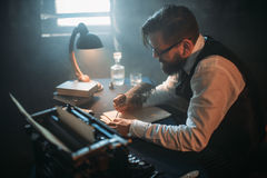 Writer in glasses writes novel with a feather Royalty Free Stock Images
