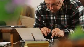 Writer with glasses writing with retro typewriter. Hd video stock video footage