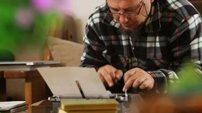 Writer with glasses writing with retro typewriter, shift focus. Hd video stock video footage