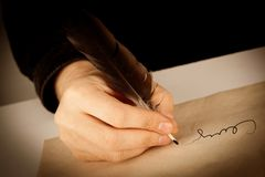 Writer holds a fountain pen over writing paper and a signature. Closeup Stock Image