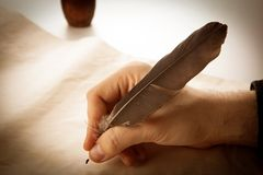 Writer holds a fountain pen over writing paper and a signature. Closeup Stock Photo