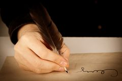 Writer holds a fountain pen over writing paper and a signature. Closeup Stock Images