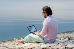 Writer with laptop. Handsome mature man working on laptop. Black-haired man in glasses typing something whe the sun is shining Royalty Free Stock Photos