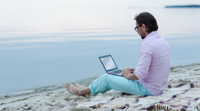 Writer with laptop. Mature freelancer working on laptop. Author in glasses writing poem at the beach. He is becoming inspired by the beautiful sea Stock Image