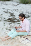 Writer with laptop. Middle-aged poet working on his laptop. Businessman in glasses making diagrams for new projects in the evening near by sea Stock Photo