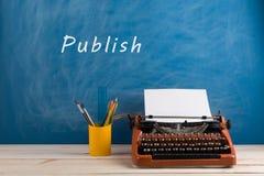 writer' local de trabalho de s - máquina de escrever e artigos de papelaria no fundo azul do quadro-negro com texto ' Publiq fotos de stock royalty free