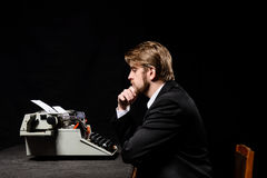 Writer, man in a black jacket typing on typewriter Royalty Free Stock Photos