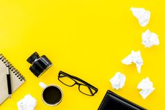 Writer office desk with notebook, ink, pen and glasses yellow background top view space for text. Writer office desk with notebook, ink, pen and glasses on royalty free stock photography