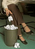 Writer's block. Woman throwing paper ball in waste basket Royalty Free Stock Image