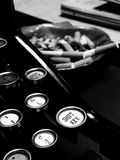 Writer`s Block. Antique typewriter with ashtray full of cigarettes in Background. in Black and White Stock Image