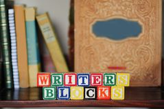 Writer's Blocks. Children's wooden blocks make a play on words of writer's block, set against a shelf of books Stock Photography