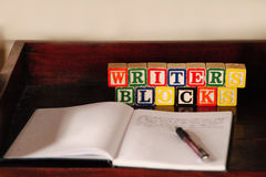 Writer's Blocks. Children's wooden blocks spell out writer's blocks, a play on words behind a notebook and pen and empty page Stock Image