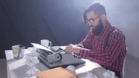 Writer`s day concept. Young male writer in a dark room typing on a typewriter. Young male writer in a dark room typing on a typewriter stock video footage