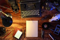 Writer`s desk table with typewriter, old phone, vintage camera, skull, supplies, cup of coffee. Top view. 3D illustration. Writer`s desk table with typewriter stock image