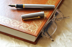 Writer's tools. Elegant book pen and glasses still life Royalty Free Stock Photos