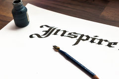 Writer`s tools. Ink, paper, pen top view. Inspire calligraphy lettering background. Word drawn with inks on sheet of paper. Drawing lessons, art school Stock Image