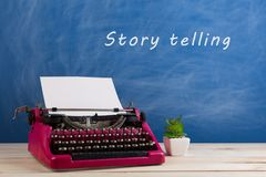 """writer's workplace - crimson typewriter on blue blackboard background and text """"Story telling stock photos"""