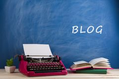 """writer's workplace - typewriter and books on blue blackboard background with text """"Blog stock photography"""