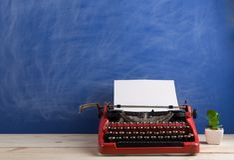 writer's workplace - red typewriter on blue blackboard background stock image