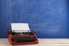 writer's workplace - red typewriter on blue blackboard background stock photo