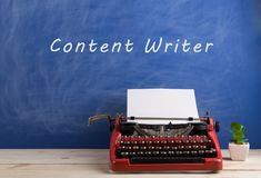 """writer's workplace - red typewriter on blue blackboard background with text """"content writer stock photo"""