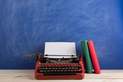 writer's workplace - red typewriter and books on blue blackboard background royalty free stock image