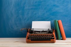 writer's workplace - red typewriter and books on blue blackboard background stock image