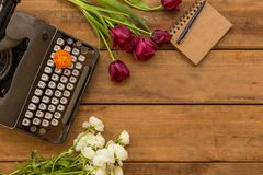 Writer spring flat lay with negative space. Writer spring flat lay with purple tulips, vintage camera, retro typewriter, white ranunculus and notepad over wooden Royalty Free Stock Photos