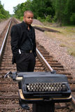 Writer on the Tracks. Young man with his typewriter on the train tracks Stock Images
