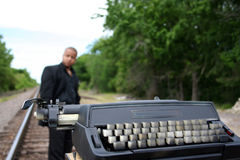 Writer on the Tracks. Young man with his typewriter on the train tracks Royalty Free Stock Image