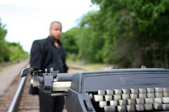Writer on the Tracks. Young man with his typewriter on the train tracks Stock Photo