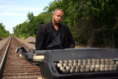 Writer on the Tracks. Young man with his typewriter on the train tracks Royalty Free Stock Images