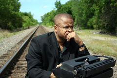 Writer on the Tracks. Young man with his typewriter on the train tracks Royalty Free Stock Photos