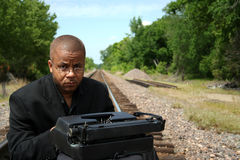 Writer on tracks. Man with typewriter on train tracks Royalty Free Stock Photo