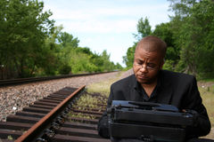 Writer on the Tracks. Young man with his typewriter on the train tracks Stock Image