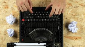 Writer typing text on a typewriter throws out a sheet. View from above. Writer types the text of the book on a typewriter, he does not like the chapter, he stock footage