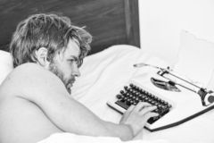 Writer use manual typewriter daily work. Man writer lay bed working on new book. New day brings fresh ideas. Writer. Author used old fashioned machine instead royalty free stock photos