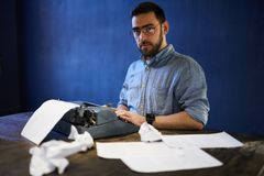 Writer at Work. Portrait of bearded writer looking at camera while using old typewriter, copy space stock photos