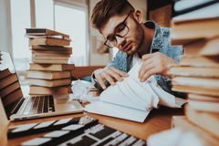 Writer Working on Laptop Sits with Stack of Books stock photo