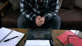 Writer working on retro typewriter, looking straight to the camera, tilt, 4K. Hd video stock footage