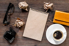 Writer workplace with vintage notebook, pen, glasses and coffee on wooden table background top view mockup Royalty Free Stock Photography