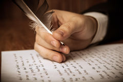 Writer writes a fountain pen on paper work Royalty Free Stock Image