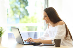 Writer writing on a laptop in a warm place Royalty Free Stock Photo