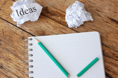Writers block. Ideas written on a crumpled piece of paper next to a note pad Royalty Free Stock Photos
