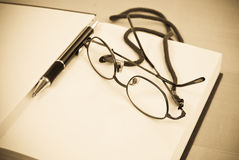 Writers Block. With Glasses And Pen On Blank Book Page Royalty Free Stock Photography
