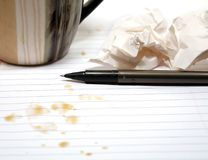 Writers Block. Black pen and crumbled paper on coffee stained paper with coffee mug Stock Image