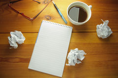 Writers block. Blank notepad with copyspace surrounded by scrunched up pieces of paper symbolising writers block or brainstorming new ideas Stock Photos