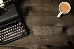Writers Block. Old fashioned typewriter on wood desktop with coffee mug focus on wood desktop for copy space use Stock Photography